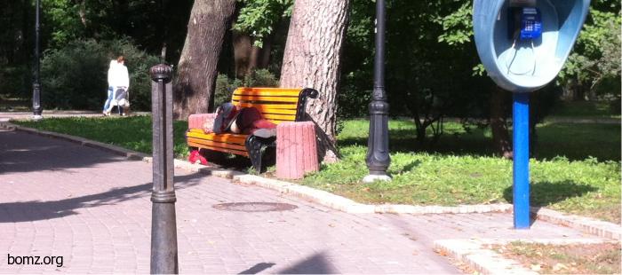 Бомж спит на лавочке в парке